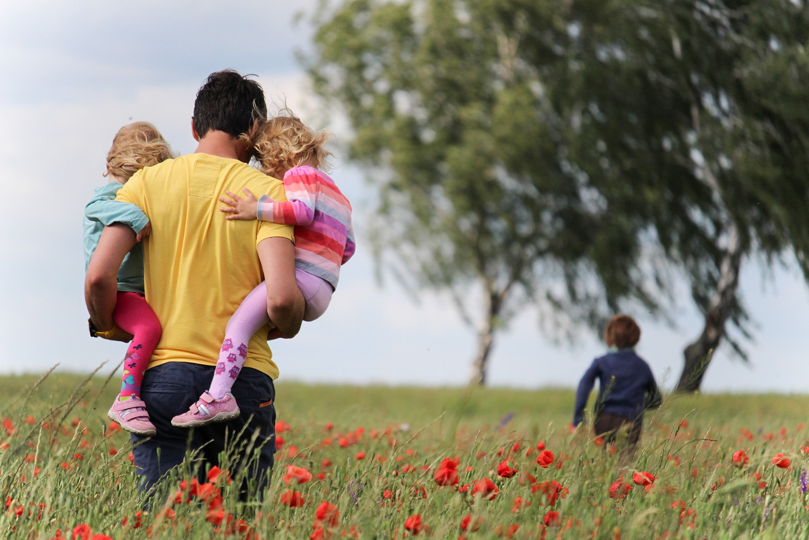 A father carrying two young children and one young child running ahead in a field with trees.