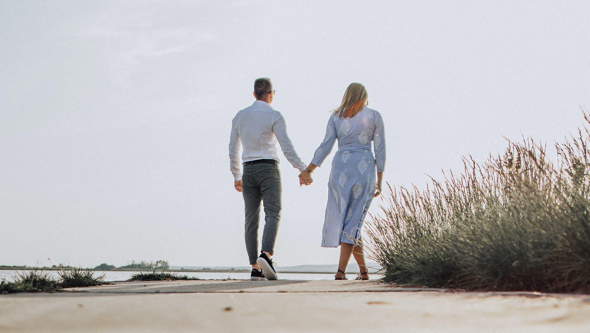 Couple holding hands walking along a beach.