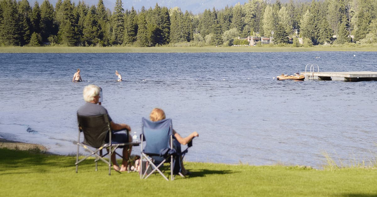 A retired couple sitting on the shore of a lake.