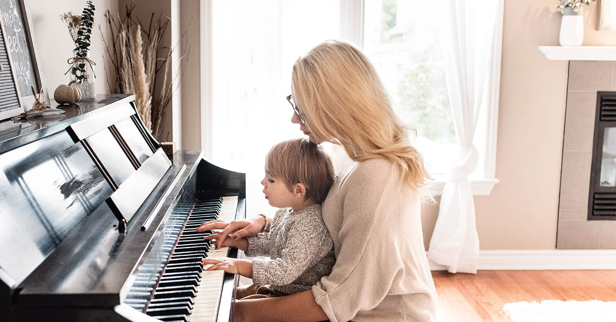 A mother holding her child while playing a paino.